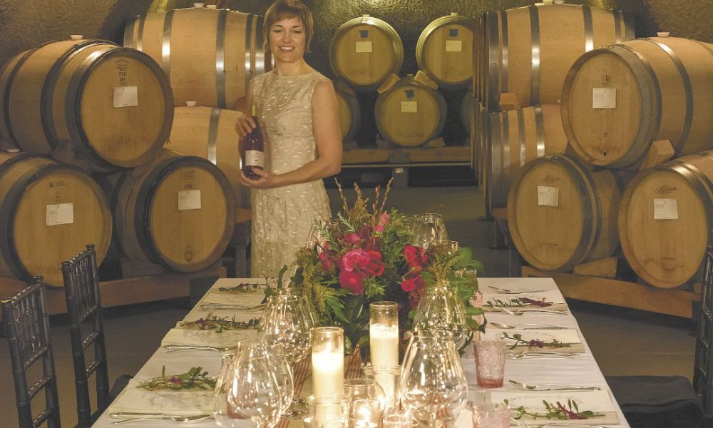 "Andrea Carpenter readies the table for a special dinner titled ""LOVE"" hosted inside Archery Summit's barrel caves. The feast featured chocolate in every course with wine pairings from the winery.##Photo by Andrea Johnson"