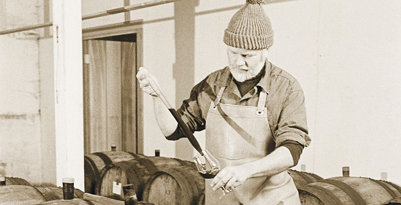 David checks on Pinot Noir in barrel during the vintage of 1983.##Photo by Tom Ballard
