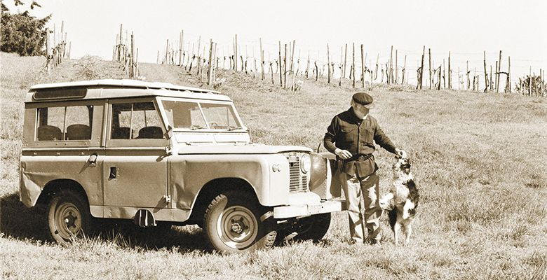 David Lett plays with his Border Collie, Tibby, next to his 1967 Land Rover 88 series in 1991 at Eyrie's vineyard.##Photo by Tom Ballard