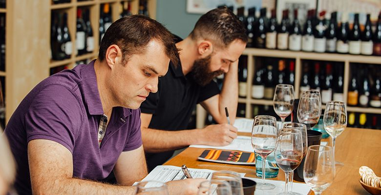Students Kevin Franck (left) and Sean Curtin study a handout during class at The Wine & Spirit Archive (WSA).
