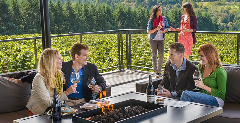 Friends gather around the fire pit with glasses of wine and small plates from the menu.##Ponzi photo by Polara Studios
