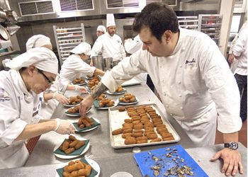 Host chef Rocky Maselli (right) prepares pheasant and ham croquettes with fired Oregon black truffle at last year's Grand Dinner with help from the staff from the Lane Community College Culinary Institute. Photo by David Barajas.