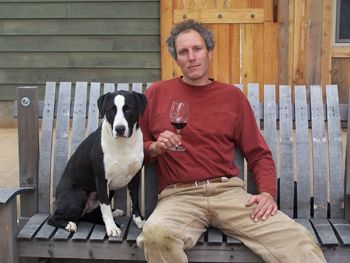 Alexis Pouillon and his dog, T-Bone, relax in front of Domaine Pouillon.