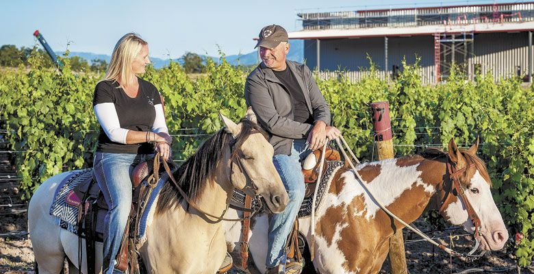 Owners Jen and Ross Allen often ride the vineyard's perimeter — the new winery is shown under construction in the background. ##Photos © David Gibb Photography | www.dgibbphoto.com
