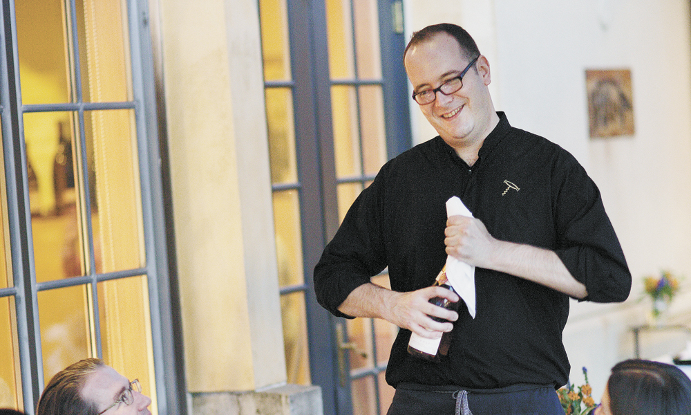 Christopher Berry, The Dundee Bistro's sommelier, opens a bottle at one of the many al fresco tables. The wine list offers many Oregon selections and some international, too. ##Photo by John Valls.