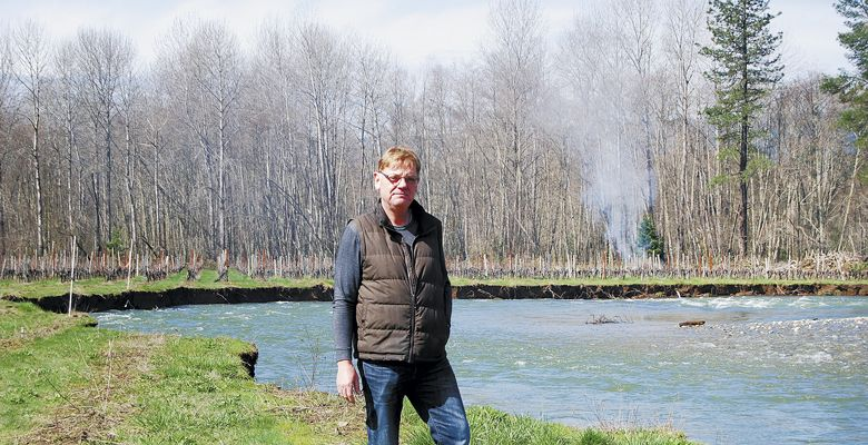 Bridgeview s Rene Eichmann stands on the eroding bank of Sucker Creek, where his vines flourished until the creek changed course this winter. ##Photo by Maureen Flanagan Battistella