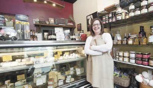 Andrea McEvoy stands in front of a deli case showcasing the cheeses available at Abbie & Oliver's.