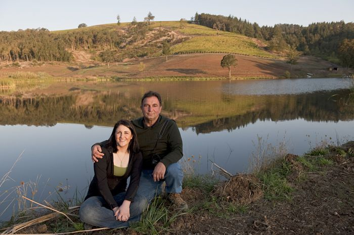 Founder Moe Momtazi and daughter Tahmiene, who oversees winemaking at Maysara Winery, pose in front of a manmade reservoir on the winery's large estate.