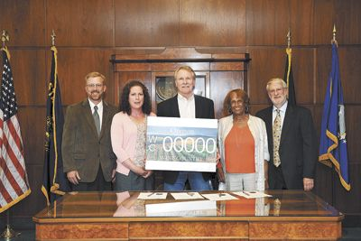 Gov. John Kitzhaber holds the proposed design for the Oregon Wine Country specialty license plate that will be available to Oregonians next year.