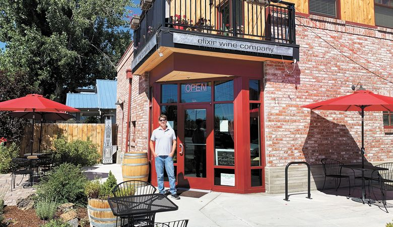 Kirk Ermisch, owner of Elixir Wine Group, stands in front of his storefront in Bend. ##Photo by Patty Mamula