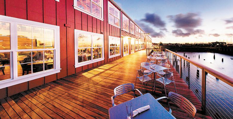 The boardwalk at Bridgewater Bistro glows from the lights inside. During the day, these seats fill with diners opting for fresh sea air. ##Photo provided.