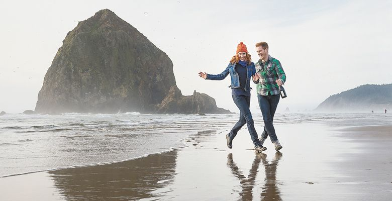 A young couple in love walk on the Oregon coast near Haystack Rock in Cannon Beach. ##Photo by Andrea Johnson.