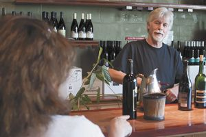 Patrick McElligott talks with a customer at the Oregon Wine Tasting Room near McMinnville, which he managed for 28 years.
