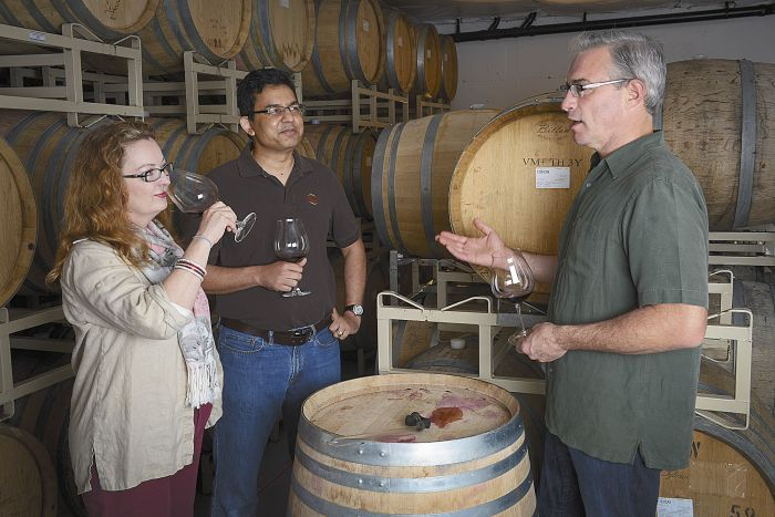 Tony Rynders discusses wine with Saffron Fields owners Sanjeev Lahoti and Angela Summers. Rynders is the red winemaker for the Yamhill-Carlton winery. Photo by Andrea Johnson