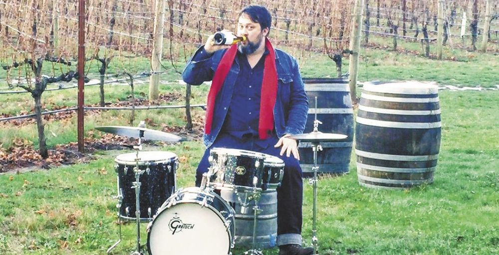 Andy Young multitasking in the vineyard. ##Photo by Michael Alberty