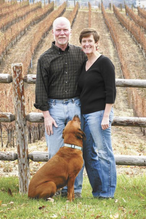 Patrick Flannery and Paula Brown stand in front of estate vines with their 7-year-old vineyard pooch, Vino.