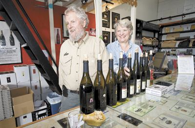 Myron Redford and Viki Wetle, co-owners of Amity Vineyards, beam from behind the tasting bar at the winery. Photo by Marcus Larson,News-Register