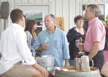 Sam talks with guests at a summertime Amity DIG event. Photo provided.