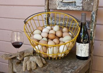 A rustic still life of freshly gathered eggs, garden gloves and a bottle of Big Table Farm wine.
