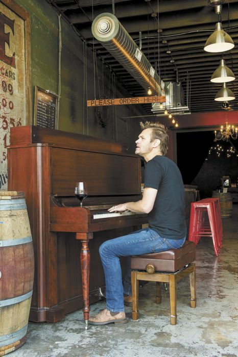 ENSO winemaker/owner Ryan Lee Sharp plays an original song at the winery's tasting room/lounge. The turn-of-the-century piano belongs to Dave Nicolardi, an ENSO regular, who is scheduled to play at the winery every other Wednesday. Photo by Andrea Johnson.