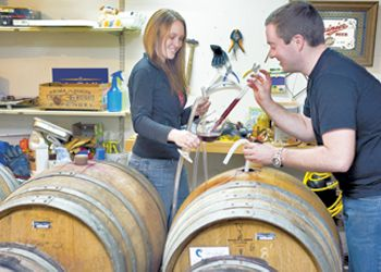 Evan and Kim Bellingar taste the progress of their wine in barrel. Photo by Janis Miglavs.