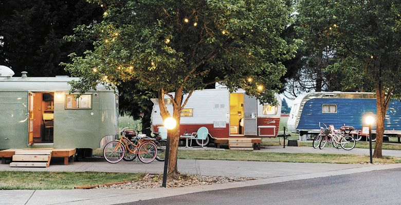 Lights glow above the trailers at The Vintages; each comes with a couple bikes for cruising the Dayton RV park. ##Photo by Kathryn Elsesser