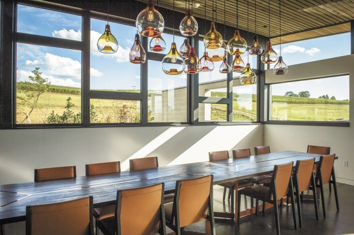 Light fixtures from Portland firm Esque Studio hang above a custom-made table inside Saffron Fields' private dining/meeting room.