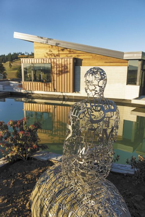 "Jaume Plensa's ""Tale Teller II,"" a life-sized sculpture crafted from stainless steel and stone sits at the edge of one of the ponds at Saffron Fields' new tasting room."