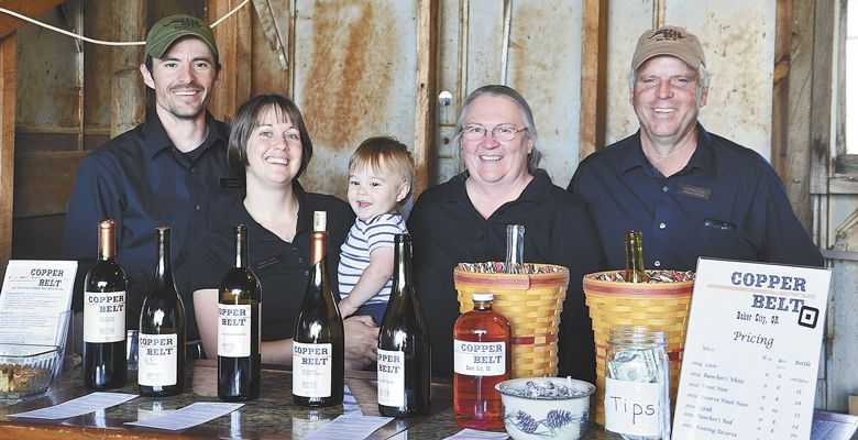 "It's a family affair at Copper Belt, from left: winemaker/founder Travis Cook; his wife, Krista, ""veterinarian supporter;"" their 2-year-old son, Nathan; his mom, Cathy, who handles the bookkeeping and marketing; and his father, Michael, Travis' ""right-hand man and workhorse of the operation."" ##Photo by Timothy Bishop"
