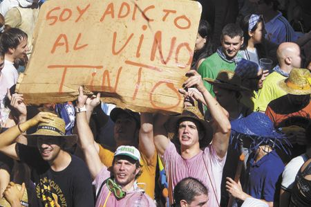 Two men in wine-stained T-shirts hold a sign in the