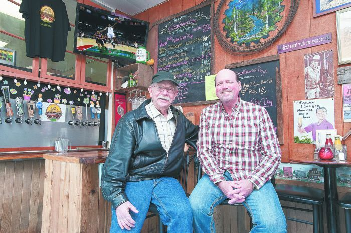 Carlton Corners' founder Vince Larson (left) and his son, Mike, inside the town's only gas station and growler pub — beer selections change regularly.