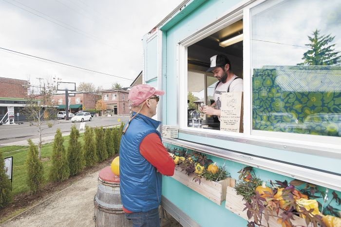 Chef Joseph Zumpano takes a customer's order from inside his food truck known as Henry's Diner.