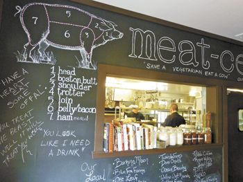 A blackboard explains Smithfields' menu through a pig diagram, lists local producers and posts pro-meat mantras.