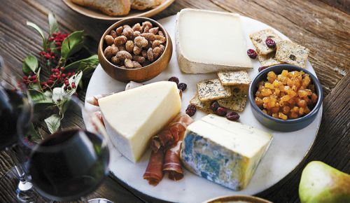 Alongside seed crackers, cured meats, almonds and dried fruit, a trio of cheeses are on display: Face 2 Face (left); Secret de Compostelle (top); Chiriboga Blue (bottom right). ##Photo by Christine Hyatt