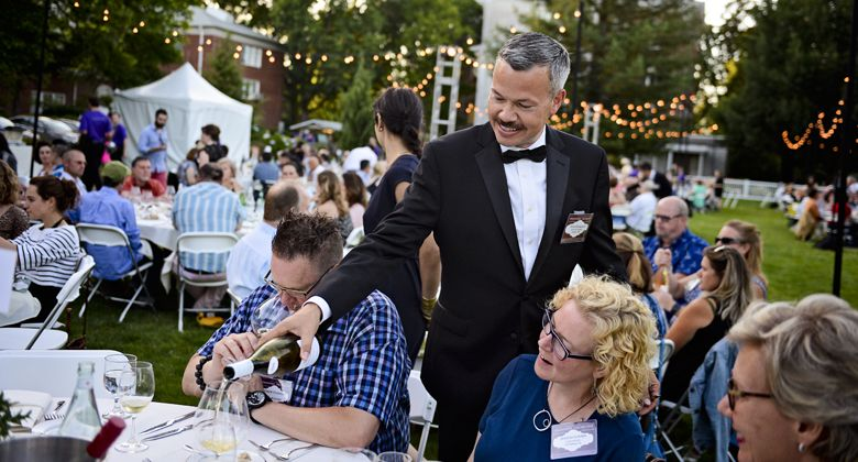 Tom Champine pours a glass of wine for a table of IPNC guests. ##Photo by Carolyn Wells-Kramer