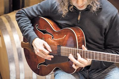 Winemaker Jay Somers strums his Eastman 605 inside his winery, J Christopher.