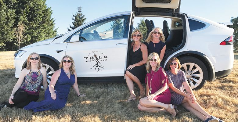 A group of wine-touring friends take a respite near their ride via Tesla Custom Winery Tours. ##Photo courtesy of Tesla Custom Winery Tours
