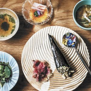 From left (top row): coastal Kombu tea; trout roe and shio koji pudding; crab custard with warm crab broth; (bottom) nasturtium leaves salad; speck; Mangaliseta ham hand roll; and honeysuckle nectar and flowers.  ##Photo by Lindsey Bolling