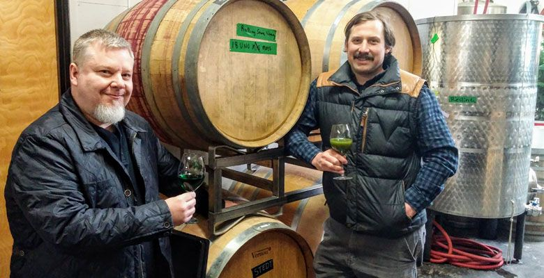 Winemakers Bryum Arnellii and Thomas Monroe salute the latest bottling of moss wine. ##Photo provided