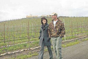Kriselle Cellars sales manager, Nora Lancaster, and operations manager, Jay Crowl, walk among the vines at the winery's estate vineyard. the 3,000-square-foot tasting room is under construction at the top of the hill.