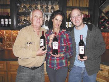 David (left), Sandy and Leon Glaser proudly hold their new wine for sale at their tasting room in Roseburg. Photo provided.