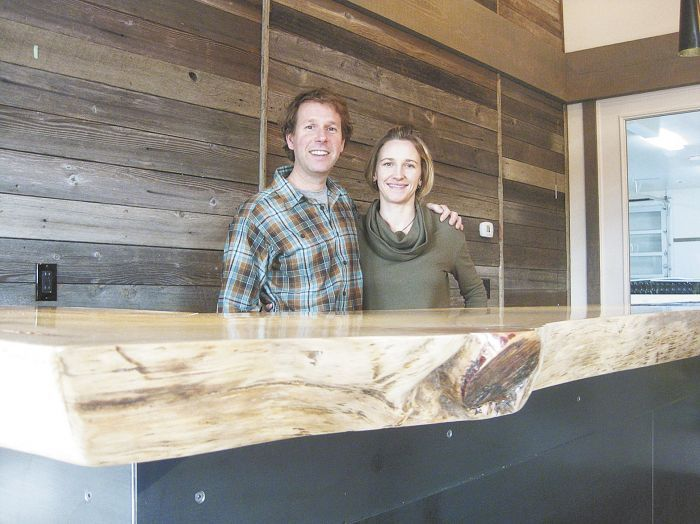 Steve Thompson and his wife, Kris Fade, behind the 100-year-old Ponderosa pine slab that anchors the interior of their tasting room featuring Analemma Wines.