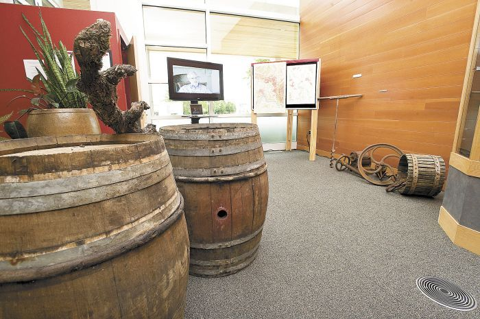 "French oak barrels and an antique wine press are part of Linfield College's Oregon wine history exhibit, ""Bringing Vines to the Valley."" Photo by Marcus Larson."