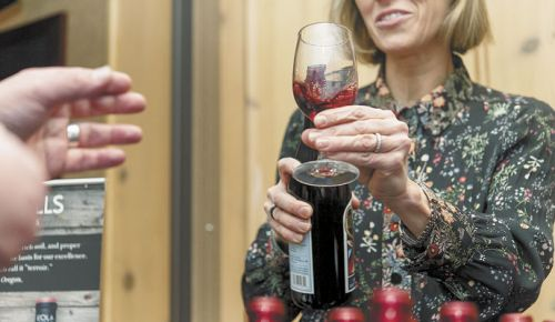 Elaine Cuyler offers a taste of Eola Hills Wine Cellars' Beaujolais-style wine during last year's Beaujolais Nouveau Festival at The Heathman in downtown Portland. ##Photo by Aubrie LeGault