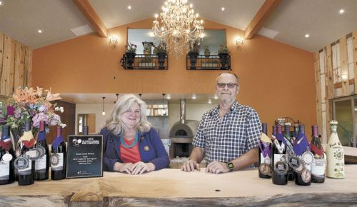 Patrik and Tess Barr stand behind the bar made from timber gathered from their Hood River property. ##Photo provided by Hood Crest
