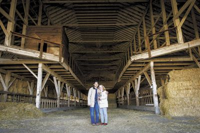 Sanjeev Lahoti and Angela Summers stand inside the huge dairy barn, which has now been dismantled for reuse in their new tasting room.