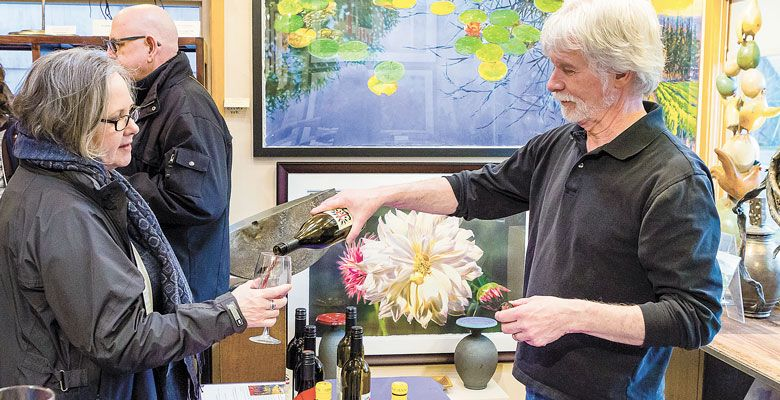 Patrick McElligott offers samples of Sineann Wine at the Northwest by Northwest Gallery during the Wine Walk. ##Photo by Chris Bidleman