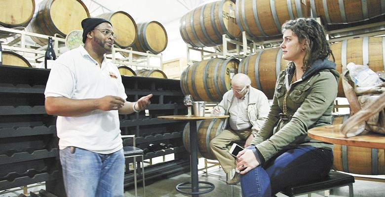 Marcus Horne, owner of Homegrown Weed & Wine Tours, chats with a participant at Duck Pond Cellars in Dundee. ##Photo by Nick Taylor