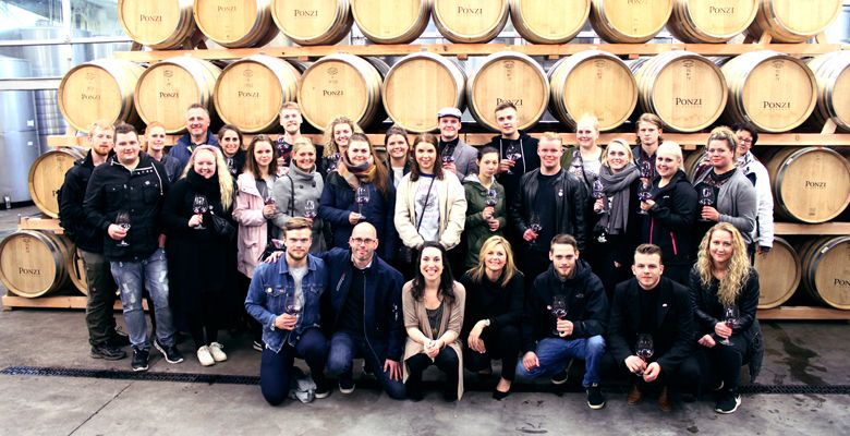 Danish students and staff receive a tour of the Ponzi barrel room. ##Photo courtesy of Ponzi Vineyards