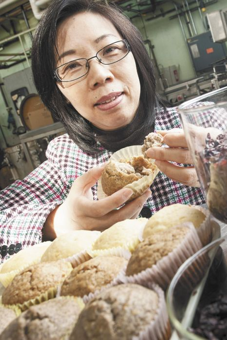 Oregon State University food science researcher Yanyun Zhao holds a muffin made with grape pomace.